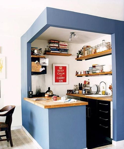 little kitchen with blue little wall on the above and side of the kitchen, wooden table top, black cabinet, brown wooden shelves