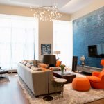 Livign Room With Wooden Floor, Brown Rug, Brown Sofa, Orange Chairs Ottoman Pillows, Beige Wall, Blue Textured Accent Wall