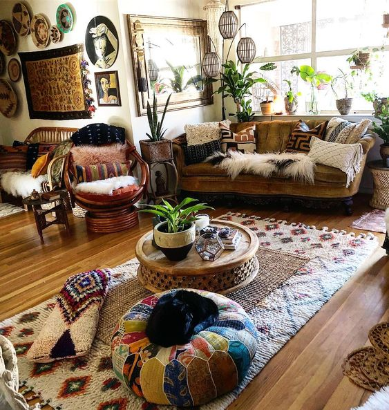 livign room with wooden floor, rug, ottoman, low coffee table, yellow velvet sofa, rattan chairs, plants, chandelier, side table, wall accessories