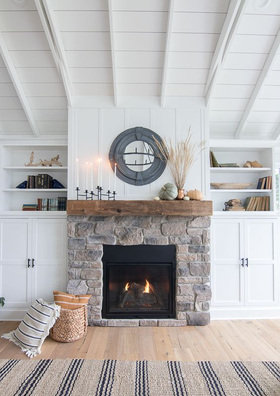 livign room with wooden floor, rug, white shelves around fireplace, wooden wall, stone covered fireplace