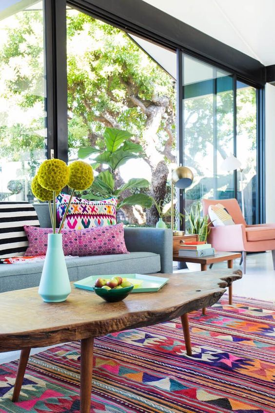 living room, white floor, colorful rug, wooden coffee table, blue sofa, colorful pillows