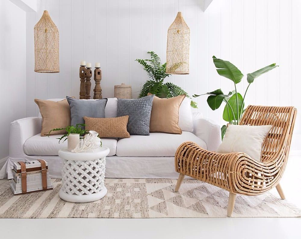 living room white floor, rug, white sofa, white round side table, white wall, pillows, rattan covered pendant, curvy wooden chair