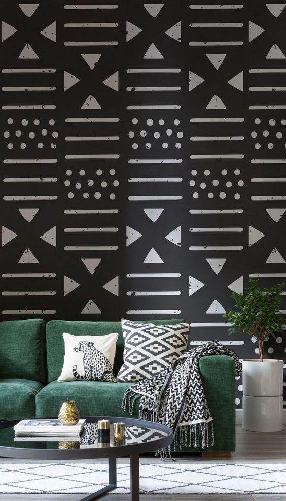 living room, white rug, green velvet sofa, round coffee table, black and white tribal wallpaper