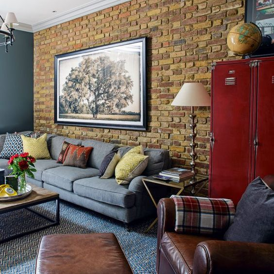 living room with blue rug flooring, grey sofa, brown leather chair, wooden coffee table, brown exposed brick, grey wall