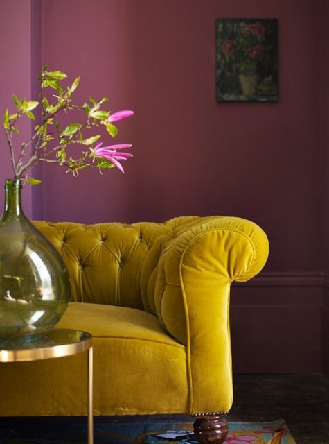 living room with dark floor, rug, pink walls, mustard sofa