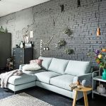 Living Room With Dark Grey Floor, Light Blue Sofa, Rug, Round Wooden Side Table, White Metal Shelves, Grey Cabinet, Grey Painted Exposed Brick Wall