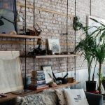 Living Room With Exposed Brick, Silver Metal Look On The Bottom Wall, Black Sofa, Wooden Shelves With Wire, Plants In Pots