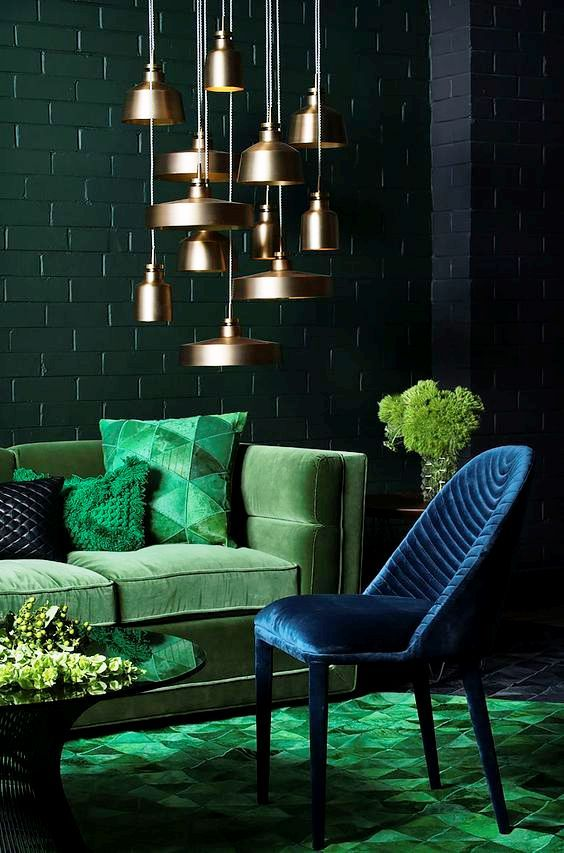 living room with green rug, blue chair, green velvet sofa, round coffee table, golden pendants, green blue painted open brick