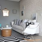 Living Room With Grey Flooring, Black White Rug, Brown Round Ottman, White Round Coffee Table, White Sofa, White Rocking Chair, Grey Wall, White Painted Open Brick