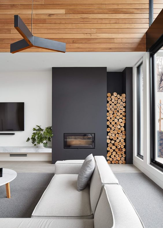 living room with grey flooring, light grey sofa, white round coffee table, white walls with TV and marble shelves under, closed traditional fireplace