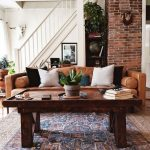 Living Room With Moroccan Rug, Wooden Coffee Table, Brown Leather Sofa, Earthy Colored Pillows