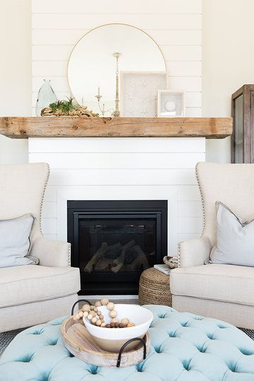 living room with rug flooring, blue buttoned round ottoman for coffee table, white chairs, white wall, wood plank accent wal in fireplace with black cover
