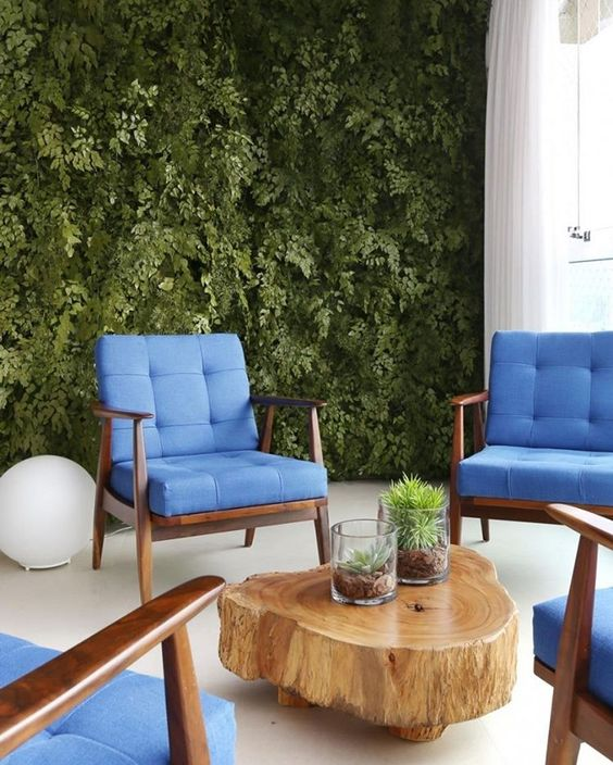 living room with white floor, blue sofa, wood slab coffee table, plants on the wall, white wall, white curtains