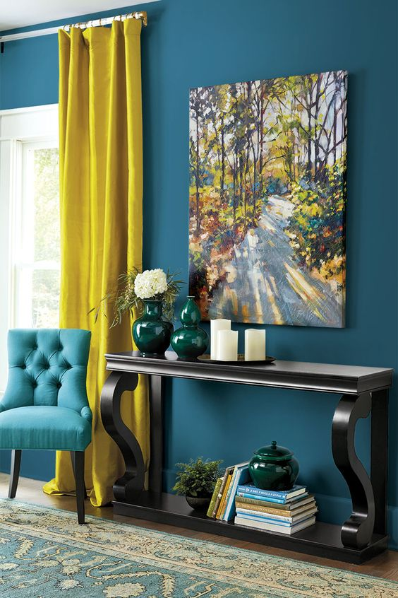living room with wooden floor, blue rug, blue wall, blue chair, wooden console table, mustard curtain