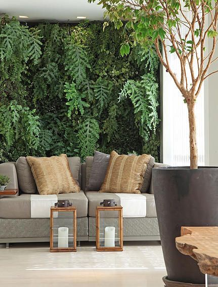 living room with wooden floor, brown sofa, small coffee tables, plants on the wall and pot