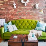 Living Room With Wooden Floor, Green Sofa, Wooden Chest As Coffee Table, Red Exposed Brick With White Wall Deoration