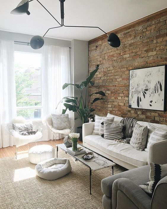 living room with wooden floor, rattan rug, white sofa, white chairs, white orroman, grey chair, white curtain, grey wall, open brick wall, plants,