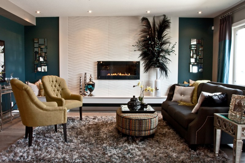 living room with wooden floor, rug, brown leather sofa, light moss green chairs, round ottoman for coffee table, green wall, white textured accent wall herringbone pattern