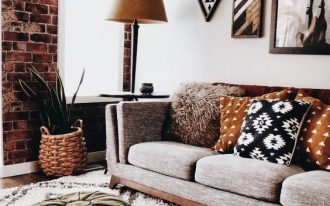 living room with wooden floor, rug, ottomans, low grey sofa, pillows, brown covered table lamps, plants, open brick accent wall