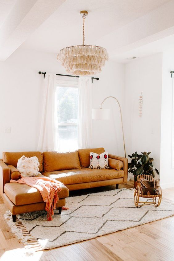 living room with wooden floor, white rug, brown leather corner sofa, white wall, fringe chandelier, white curtain