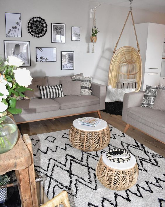 living room with wooden floor, white rug, grey sofas, bamboo swing chair, round rattan coffee table