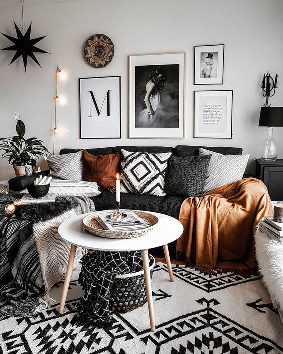 living room with wooden floor, white rug, wooden coffee table, dark sofa with dark pillows, clothes, pictures, plant