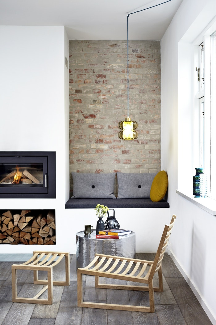 living room with wooden floor, white wall, fireplace and wood shelves under, wooden chair, alcove with seating nook, black cushon, open brick wall