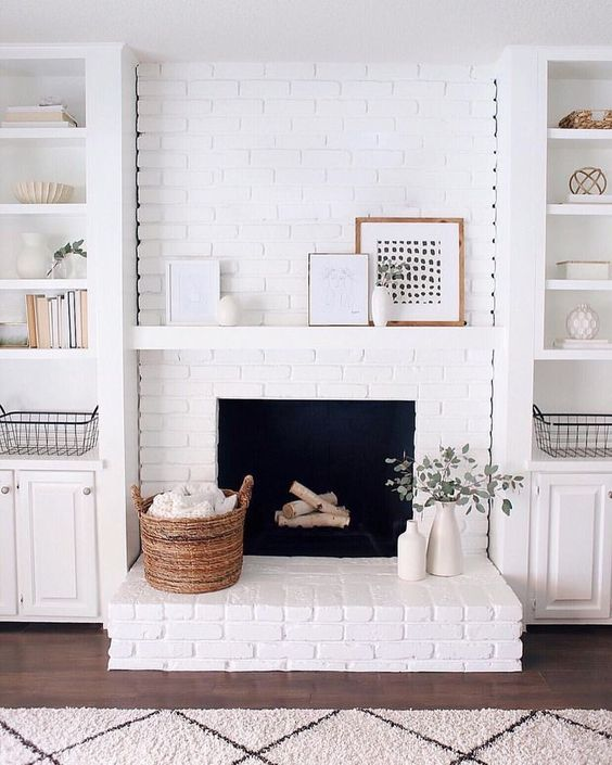 living room with wooden floor, white walls, white wooden shelves, rug, open brick accent wall painted in white