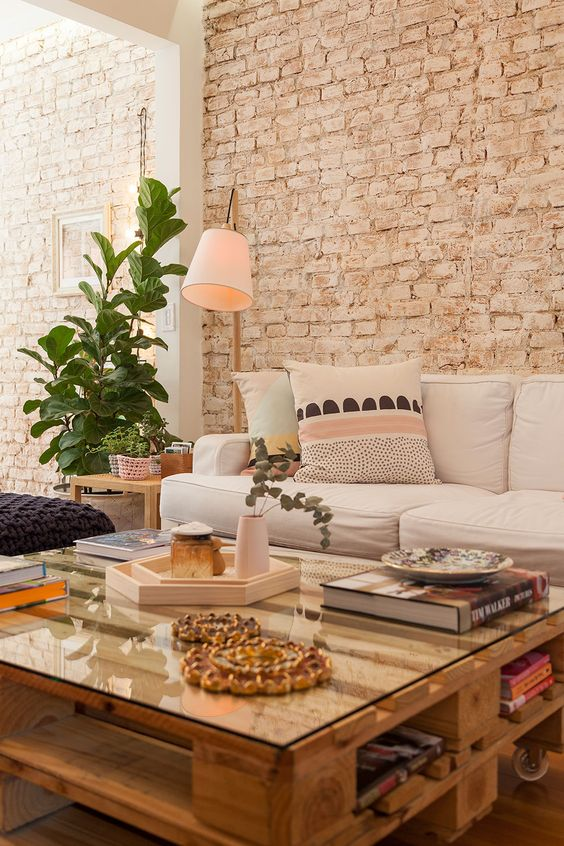 living room with wooden floor, wooden coffee table, off white sofa, purple ottoman, off white open brick wall, pink floor lamp