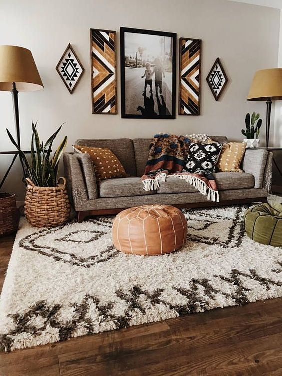 living room, wooden floor, white rug, grey sofa, brown ottoman, brown floor lamp, white walls, wall decors