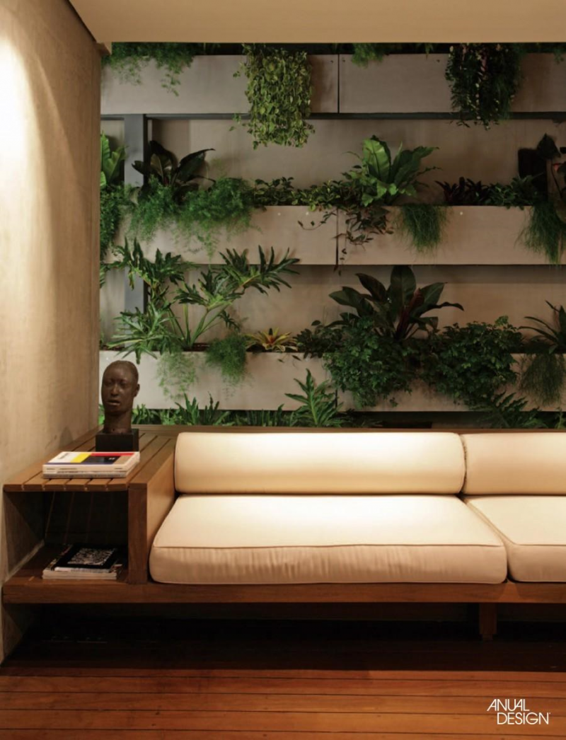 living room, wooden floor, wooden bench with white cushion, white shelves on the wall for plants,
