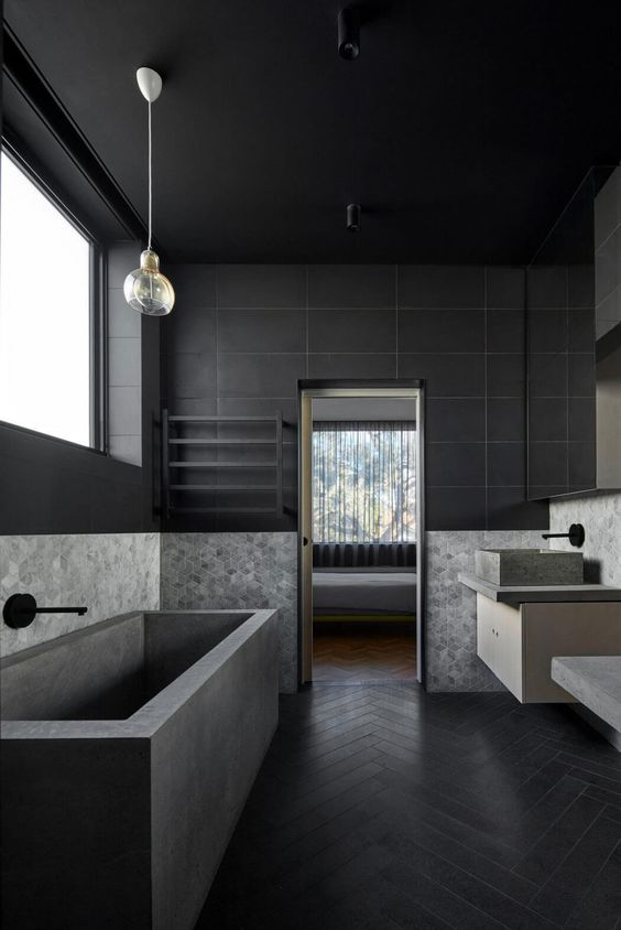 long large bathroom with black herringbone pattern floor, gery tub, grey sink with cabinet, glass pendant