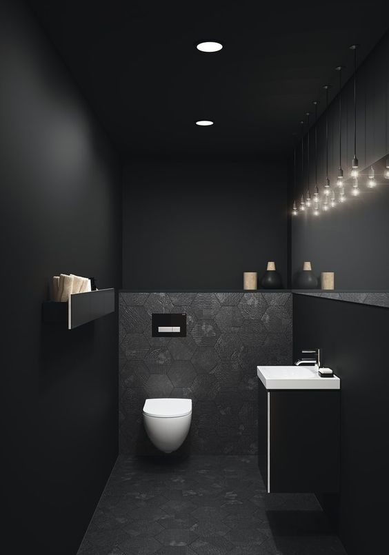 long narrow bathroom with black walls, black tiles on the floor, accent wall, white toilet, black cabinet with white top sink
