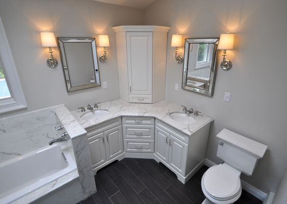 medium sized corner vanity with white marble sink, white cabinet, cornerd top cabinet, two mirrors