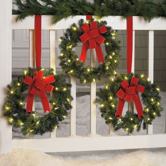 mistletoe garlands with red ribbon on the white fences outside