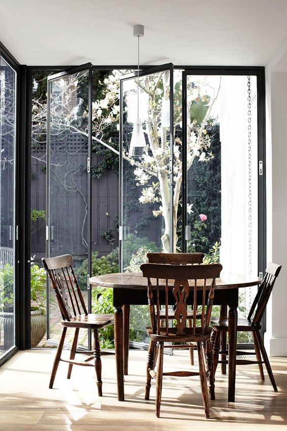 modern dining area, wooden floor, glass door wall, wooden round dining table, wooden chairs