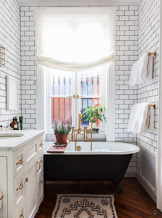 narrow bathroom with brown wood pattern tiles, rug, white cabinet with white marble top, black tub with white inside, wooden board, golden rails, white tiles wall