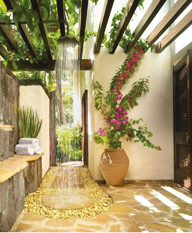 open bathroom yellow stone floor, shower from pergola, grey stone yellow stone wall, white wall,