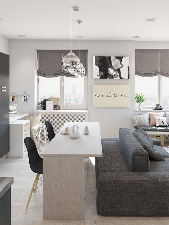 open room with kitchen, white dining table, black chairs, grey sofa with two fronts, white study area, silver pendant, wooden bench with grey cushion and pilows