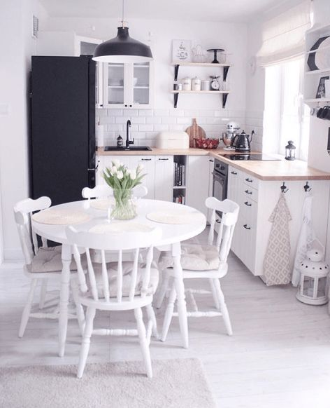open room with kitchen with white wooden, whiet glass cupboards, wooden shelves, black refrigerator, white wooden dining set