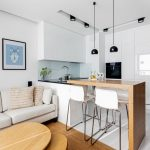 Open Room With White Wall, White Floor On The Kitchen With White Sleek Cabinet And Cupboards, Wooden Floor On The Living Room, White Sofa, Black Pendant