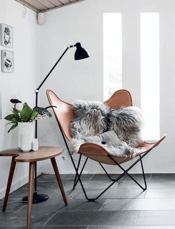 orange leather lounge chair with grey faux fur, wooden table, black floor lamp
