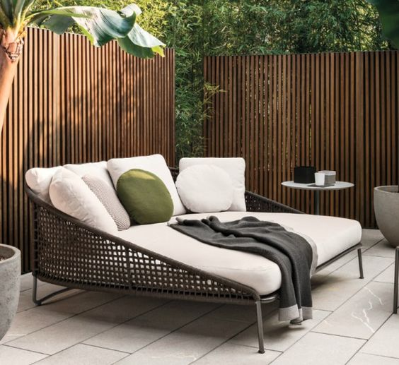 patio wide lounge chair with dark rattan material, white cushion, white pillows