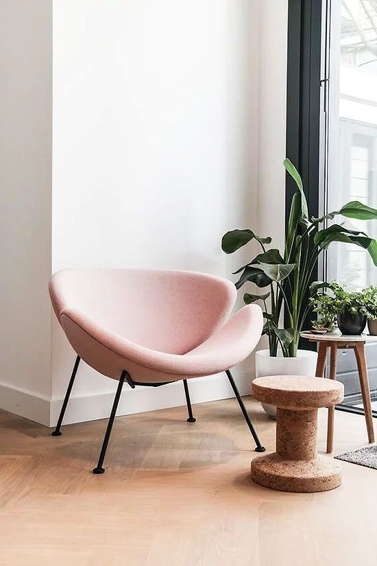 pink bowl chair with black metal support, pink cushion, plants in white pot, wooden small table nearby,