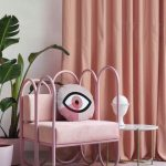 Pink Metal Chair With Pink Cushion Near White Side Table, Pink Curtain, Pillows, Plants In Pot