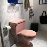 Pink Toilet With Faux Fur Cover On The Lid In A White Bathroom