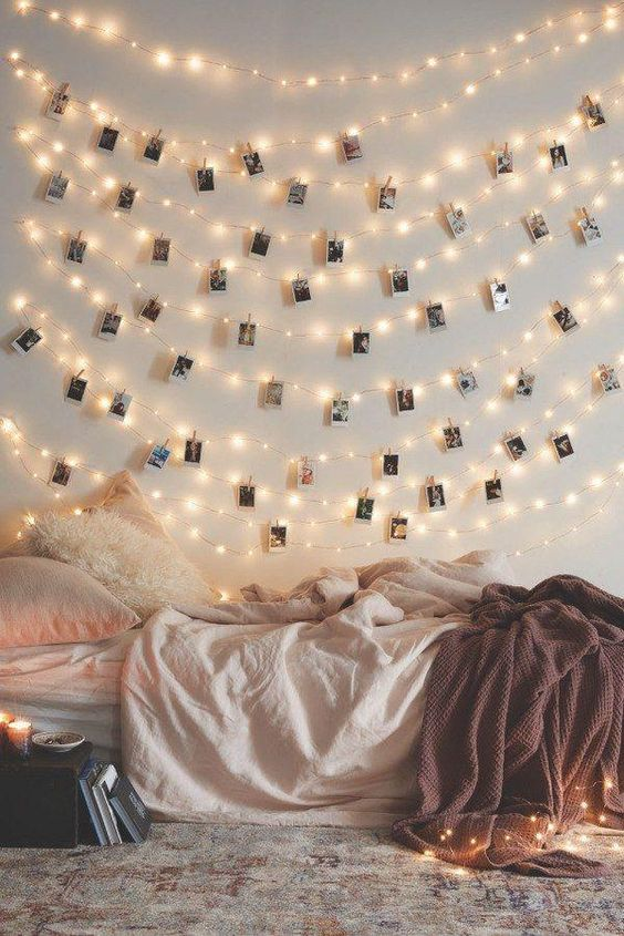 plenty of small fairy lights on the wall with pictures