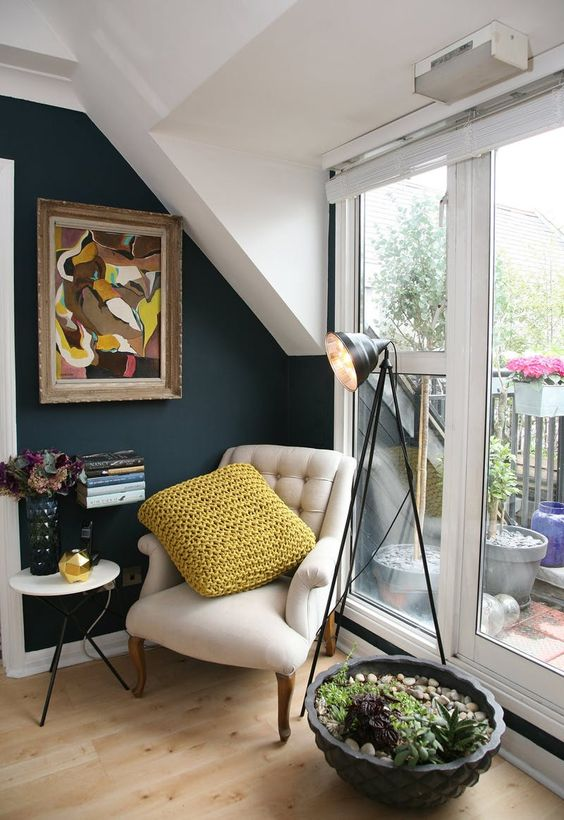 reading nook in a corner with wooden floor, beige chair, mustard pillow, white round side table, plants, floor lamp, near the balcony