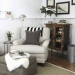 Reading Nook In A Corner With Wooden Floor, Rug, Light Grey Chair With Dark Grey Ottoman, White Wall, Wooden Cabinet, Round Side Table