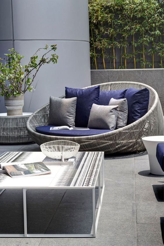 round outdoor chair with rattan woven, purple cushions, purple and grey pillows